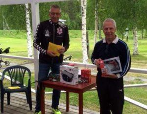 Tävlingledare Ole Lundgren delar ut pris till fjolårsvinnaren av Rossöhandlarna.